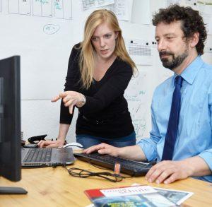 Agenturleiter Andrej Priboschek und die leitende Redakteurin Laura Millmann diskutieren die Gestaltung des